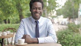 Glimlachende Afrikaanse Zakenman Sitting in Openluchtkoffie stock videobeelden