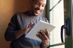 Glimlachende Afrikaanse zwarte mens die tablet thuis woonkamer gebruiken stock foto