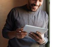 Glimlachende Afrikaanse zwarte mens die tablet thuis woonkamer gebruiken stock afbeelding