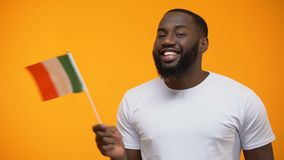 Glimlachende Afro-Amerikaanse mens die Italiaanse vlag, internationaal vriendschapsconcept houden stock video