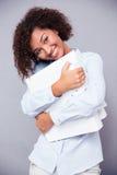 Glimlachende afro Amerikaanse vrouw die zich met omslagen bevinden Stock Fotografie