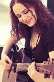 Glimlachende akoestische gitaarspeler Stock Foto's