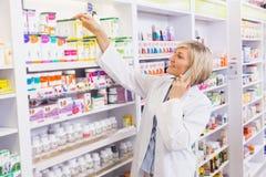 Glimlachende apotheker die en geneeskunde van plank telefoneren nemen royalty-vrije stock afbeelding