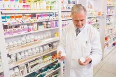 Glimlachende apotheker die medicijnen bekijken Stock Foto