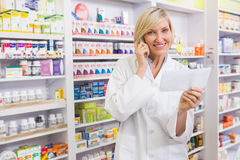 Glimlachende apotheker op het voorschrift van de telefoonlezing Stock Fotografie