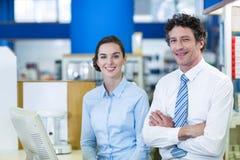 Glimlachende apothekers die zich bij teller in apotheek bevinden royalty-vrije stock foto