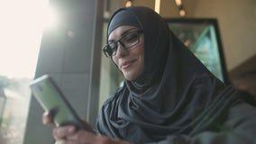 Glimlachende Arabische dame die in koffie op telefoon, toepassing babbelen voor online het winkelen stock video