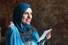 Glimlachende Arabische moslimvrouw die aan muziek luisteren