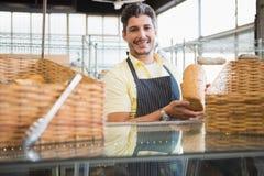 Glimlachende arbeider die een brood tonen royalty-vrije stock afbeelding
