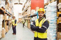 Glimlachende arbeider die geel vest met gekruiste wapens dragen stock fotografie