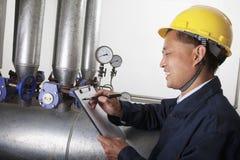 Glimlachende arbeider die het materiaal van de oliepijpleiding in een gasinstallatie controleren, Peking, China royalty-vrije stock afbeelding