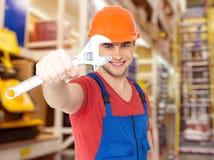Glimlachende arbeider met grote moersleutel Stock Afbeelding