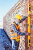 Glimlachende arbeider in weerspiegelend vest en bouwvakker die met waterpas werken royalty-vrije stock foto