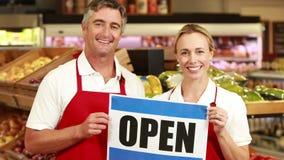 Glimlachende arbeiders die open teken houden stock videobeelden