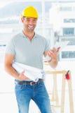 Glimlachende architect met blauwdrukken en klembord in bureau Royalty-vrije Stock Afbeeldingen