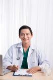 Glimlachende arts die aan computer bij zijn bureau in medisch bureau werken Royalty-vrije Stock Foto