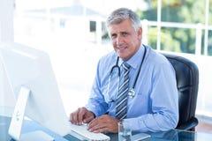 Glimlachende arts die aan computer bij zijn bureau werken Royalty-vrije Stock Afbeeldingen