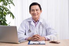 Glimlachende arts die aan computer bij zijn bureau werken Royalty-vrije Stock Afbeelding