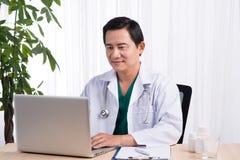 Glimlachende arts die aan computer bij zijn bureau werken Stock Fotografie