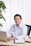Glimlachende arts die aan computer bij zijn bureau werken Royalty-vrije Stock Foto