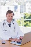Glimlachende arts die aan zijn laptop werken Royalty-vrije Stock Foto