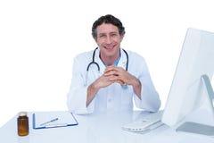 Glimlachende arts die aan zijn laptop werken Royalty-vrije Stock Foto's
