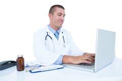 Glimlachende arts die aan zijn laptop werken Stock Afbeelding