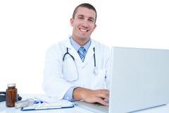 Glimlachende arts die aan zijn laptop werken Stock Foto