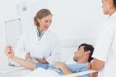 Glimlachende arts die bloeddruk van een patiënt meten royalty-vrije stock afbeelding