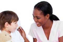 Glimlachende arts die de temperatuur van het kind vergt Stock Fotografie