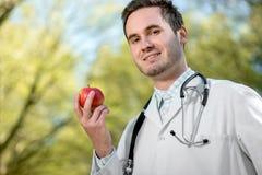 Glimlachende arts die een appel in hand houden Royalty-vrije Stock Foto's