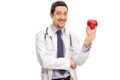 Glimlachende arts die een appel houdt Royalty-vrije Stock Afbeelding