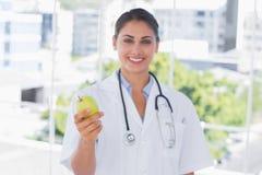Glimlachende arts die een groene appel houden Royalty-vrije Stock Afbeeldingen