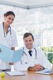Glimlachende arts die een omslag tonen aan een collega stock foto