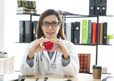 Glimlachende arts die een rood hart houden royalty-vrije stock foto