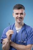 Glimlachende arts die en bij camera stellen glimlachen Stock Foto