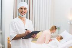 glimlachende arts die iets schrijven aan klembord in het ziekenhuis en het kijken royalty-vrije stock foto