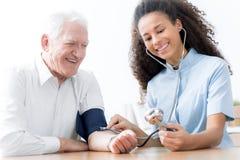 Glimlachende arts die met stethoscoop gelukkig bejaarde in t onderzoeken stock foto's