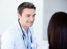 Glimlachende arts die met zijn patiënt spreekt Stock Foto