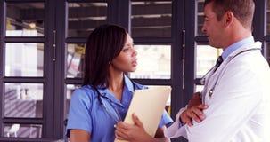 Glimlachende arts die met zijn verpleegster spreken stock footage