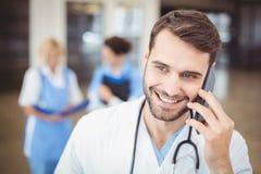 Glimlachende arts die op mobiele telefoon spreken Stock Foto