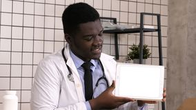 Glimlachende arts die product op een tabletcomputer voorstellen Witte vertoning stock video