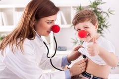 Glimlachende arts die succeskind met omhoog vinger onderzoeken Stock Foto
