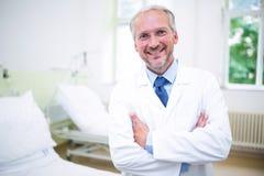 Glimlachende arts die zich met gekruiste wapens bevinden stock foto