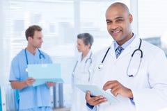 Glimlachende arts die zijn tablet gebruiken Royalty-vrije Stock Afbeelding