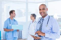 Glimlachende arts die zijn tablet gebruiken Royalty-vrije Stock Afbeeldingen
