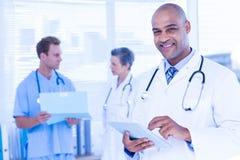 Glimlachende arts die zijn tablet gebruiken Stock Foto's