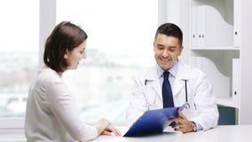 Glimlachende arts en jonge vrouwenvergadering bij het ziekenhuis stock footage