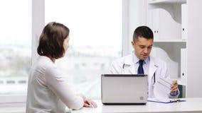 Glimlachende arts en jonge vrouwenvergadering bij het ziekenhuis stock videobeelden