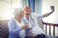 Glimlachende arts en patiënt die een selfie nemen Stock Afbeelding